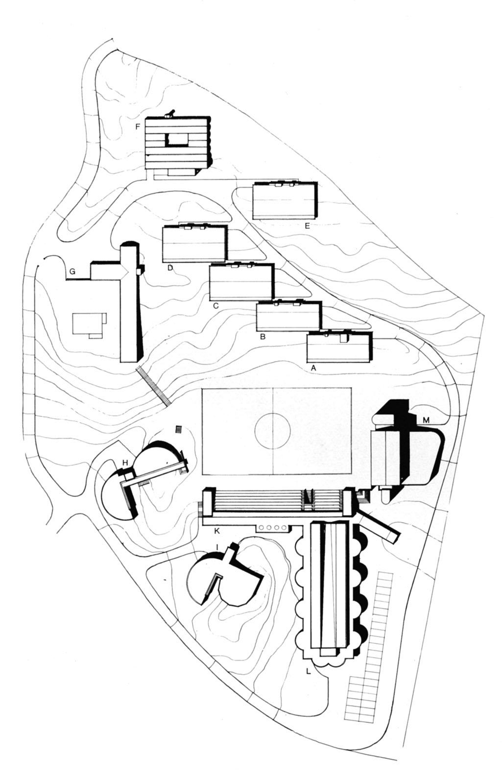 Location plan, Skådalen school, 1975. A., B., C., D., E.Children's dormitories, F.Dormitory, youth 16-18, G.Administration, H.Observation wing, I.Pre-school, K.Main entrance, L.Activities wing, M.Swimming pool.
