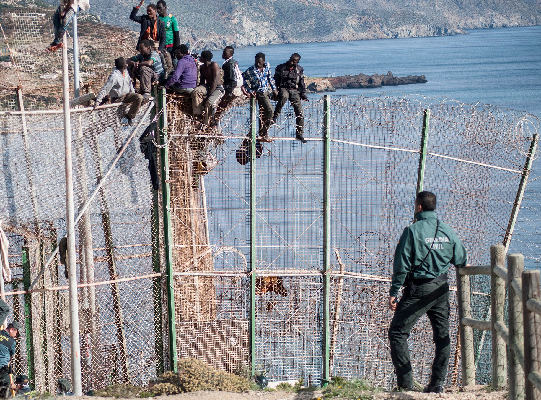 African migrants sit on top of a border fence between Morocco and Spain's north African enclave of Melilla during an attempt to cross into Spanish territory, 3rd April, 2014. Photo: NTB SCanpix.